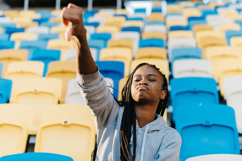 The disappointed afro-american teenager is showing the thumb down while watching the match on the stadium. royalty free stock photography