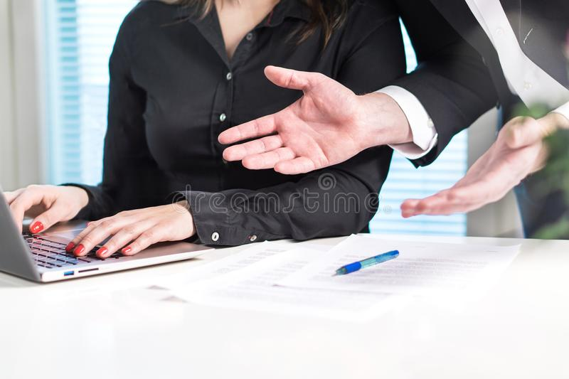 Disappointed or angry boss yelling at employee. Unhappy manager talking to bad assistant or secretary. Businessman spreading hands in office with coworker stock photo