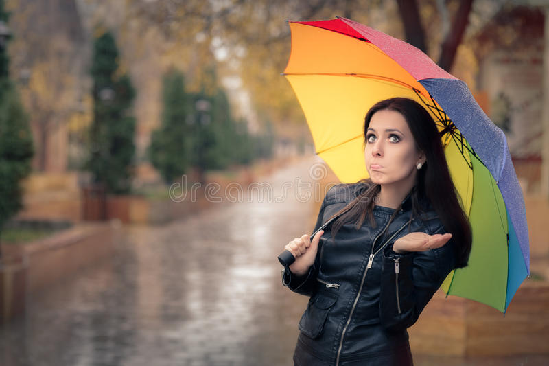 Disappointed Autumn Girl Holding Rainbow Umbrella. Sad fall girl wearing leather jacket outside in rainy weather royalty free stock image