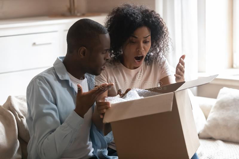 Disappointed biracial client couple frustrated by wrong order. Disappointed biracial husband and wife unpack cardboard box get wrong order, frustrated african stock image