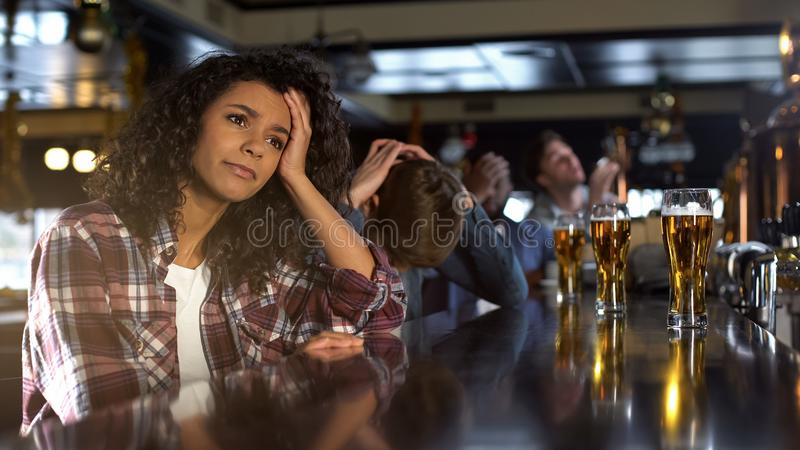 Disappointed biracial female with male friends watching sport game in bar, loss stock image