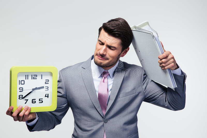 Disappointed businessman holding folders and clock. Over gray background stock photos