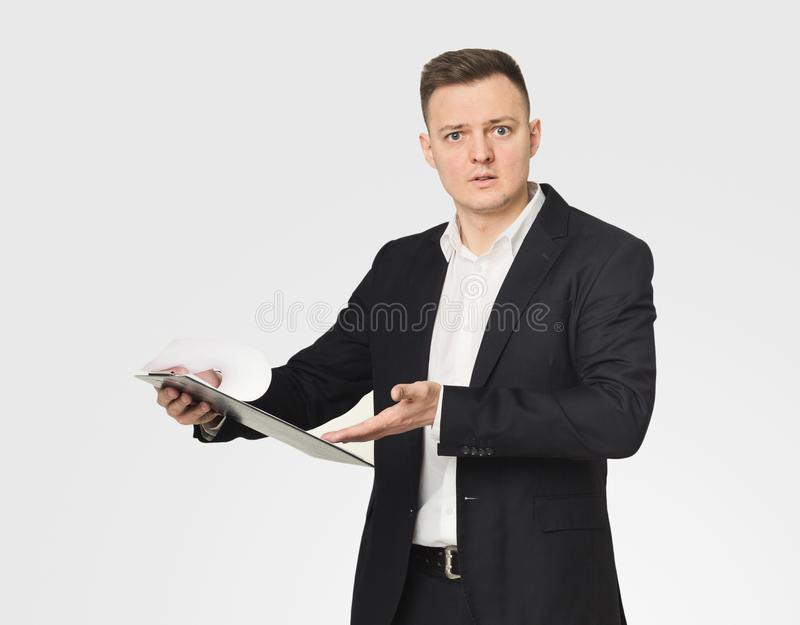 Disappointed businessman reading documents. Disappointed young caucasian businessman reading documents in notepad, found mistake in report, white background royalty free stock photos