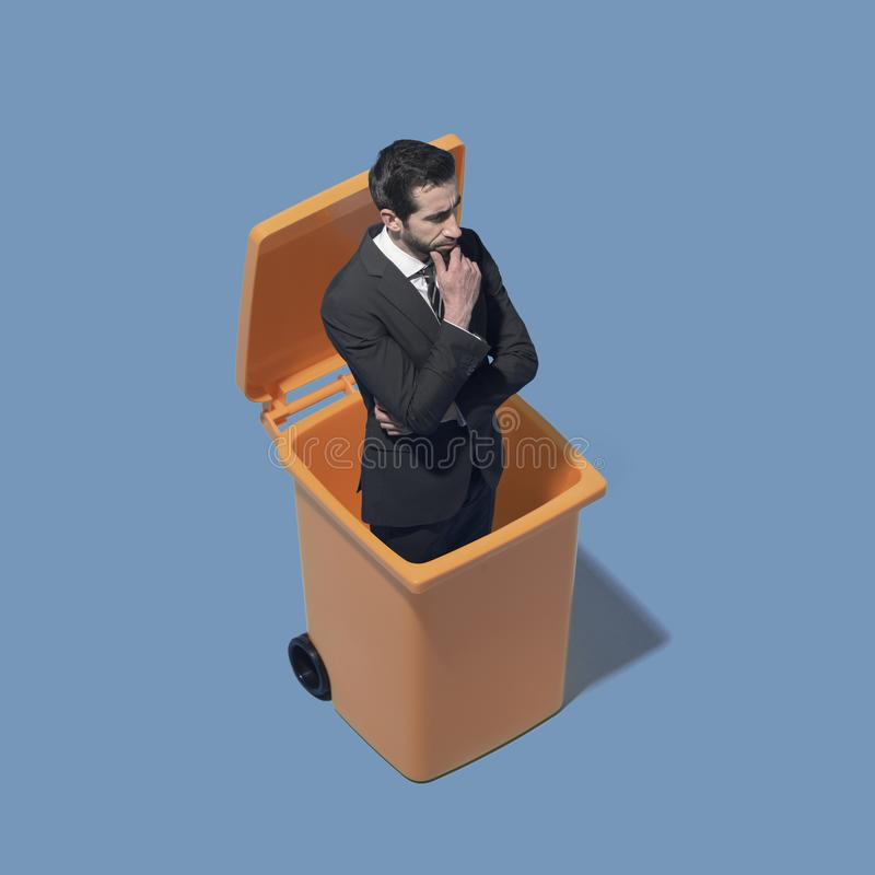 Disappointed corporate businessman standing in a trash bin. He has been discharged royalty free stock photography