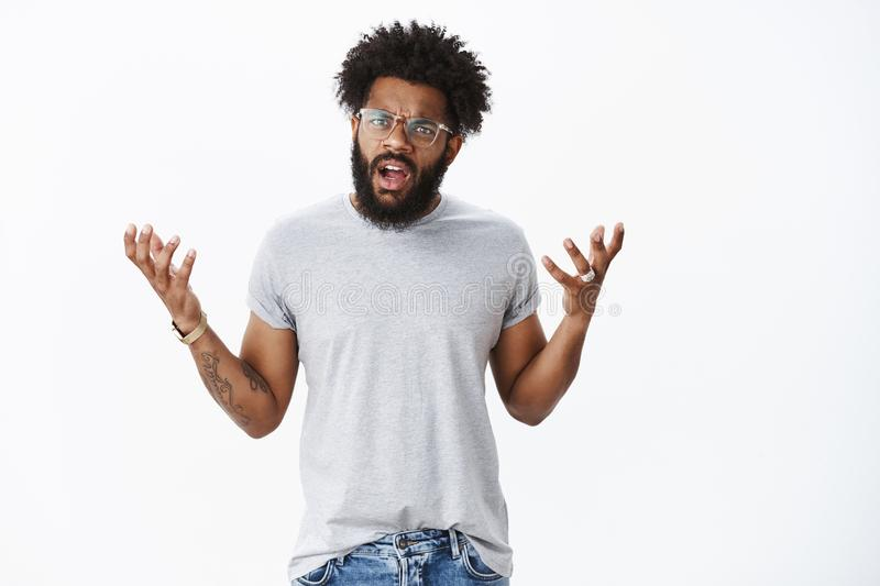 Disappointed customer arguing being pissed with service. Portrait of displeased angry young african american man in. Glasses with tattoos and piercing shrugging royalty free stock images