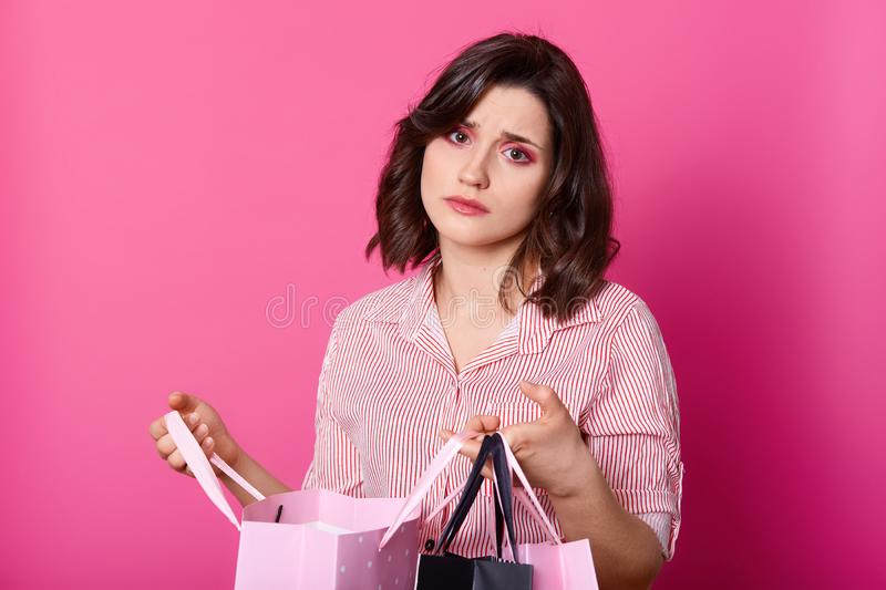 Disappointed dark haired woman, wears rose blouse, holds opened bag. Beautiful brunette looks unhappy, dislikes purchase. Bored royalty free stock photo
