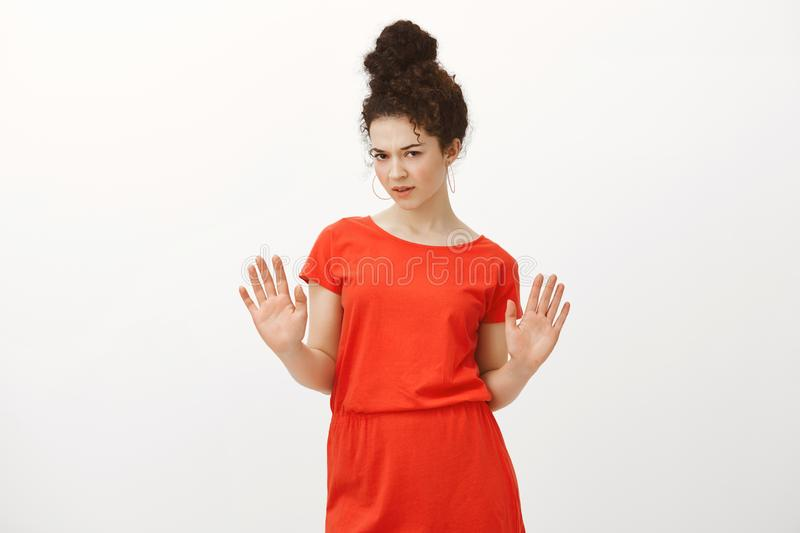 Disappointed doubtful attractive female coworker in stylish red dress, raising palms in no or stop gesture, looking from. Under forehead with displeasure and royalty free stock image