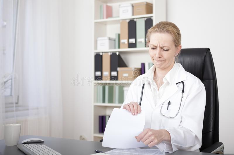 Disappointed Female Doctor Tearing Some Papers. Disappointed Adult Female Doctor Tearing Some Medical Documents While Sitting at her Office stock photography