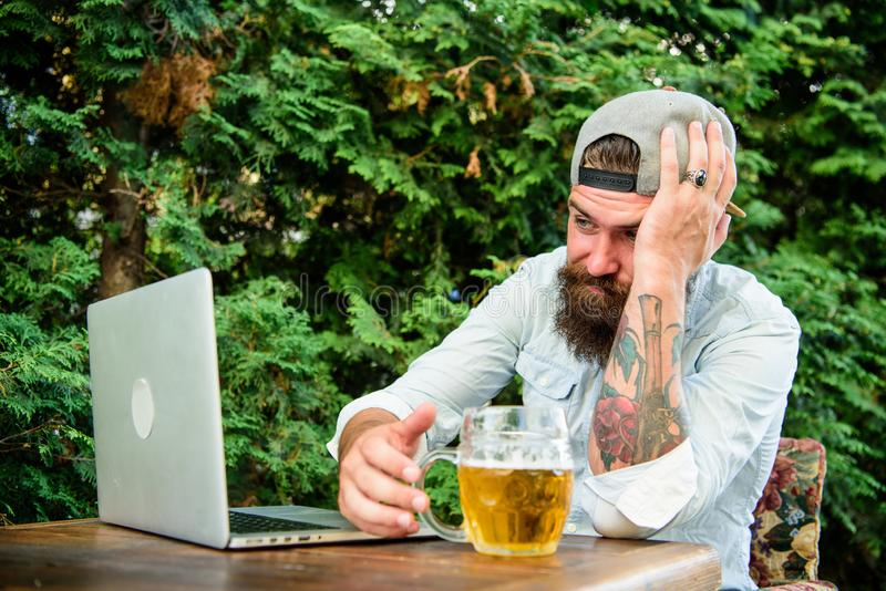 Disappointed with game result. Brutal man leisure with beer and sport game. Fan watch stream online while sit terrace. Outdoors drink beer. Football fan bearded royalty free stock photos