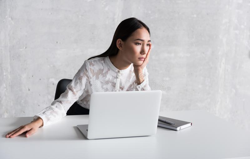Disappointed glancing woman sitting near desk royalty free stock photos