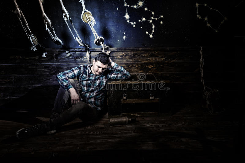 Disappointed guy sits near a chest, holding glass bottle and try royalty free stock image