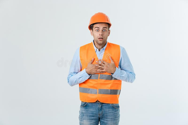 Disappointed handsome engineer wearing orange vest and jeans with helmet, isolated on white background.  stock photo