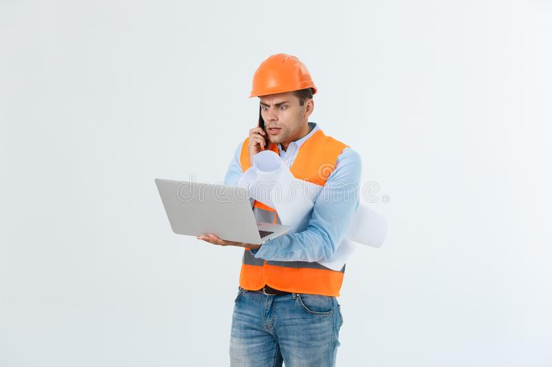 Disappointed handsome engineer wearing orange vest and jeans with helmet, isolated on white background.  stock photography