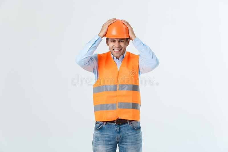 Disappointed handsome engineer wearing orange vest and jeans with helmet, isolated on white background.  royalty free stock images