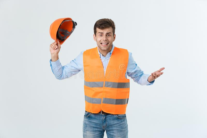 Disappointed handsome engineer wearing orange vest and jeans with helmet, isolated on white background.  stock images