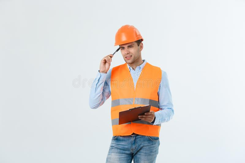 Disappointed handsome engineer wearing orange vest and jeans with helmet, isolated on white background.  stock image