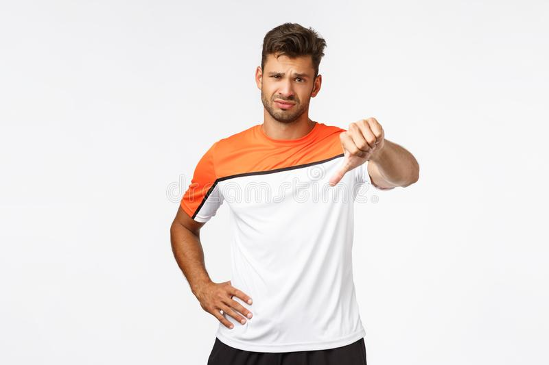 Disappointed handsome sportsman, football player displeased of someone weak attitude, show thumb-down frowning and royalty free stock image