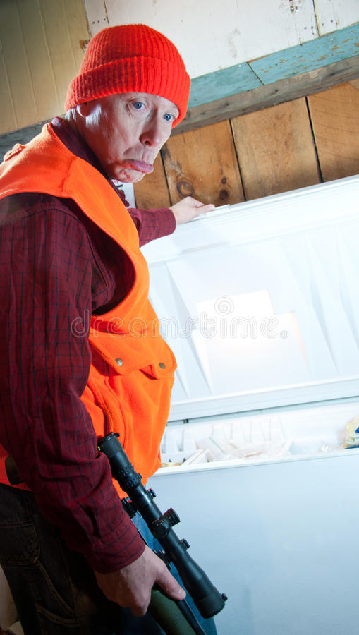 Disappointed hunter. A hunter stands with his rifle in front of an open freezer royalty free stock photos
