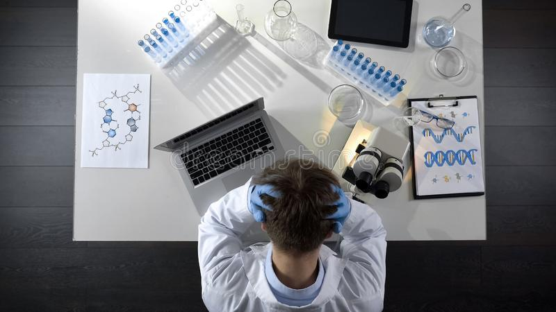 Disappointed laboratory worker sitting upset by experiment failure, top view royalty free stock photo