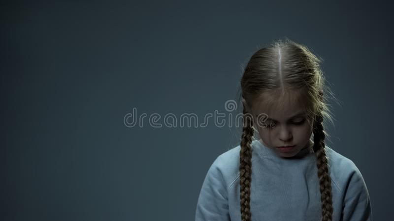 Disappointed little child looking down, orphan girl missing parents, homeless royalty free stock image