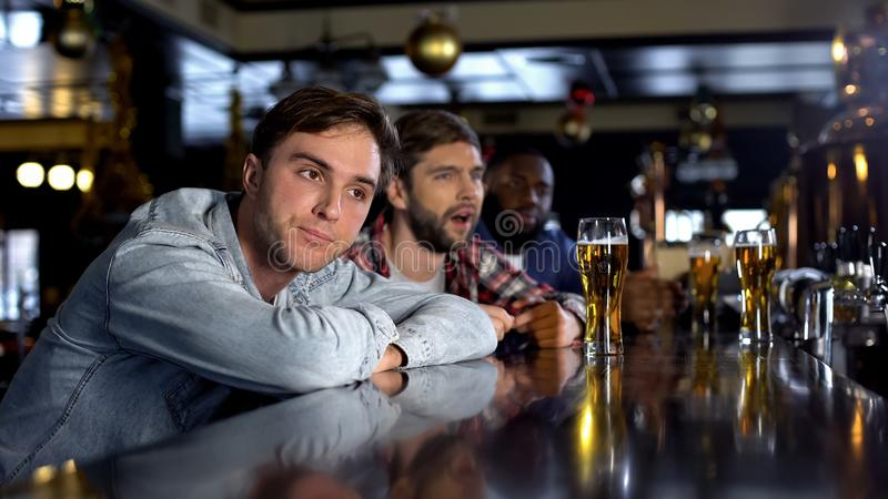 Disappointed male friends watching game in pub, disappointed with losing match. Stock photo stock images