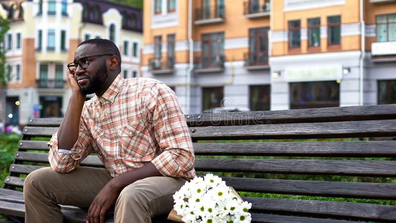 Disappointed male sitting lonely on city bench with flower bouquet, failed date stock photos