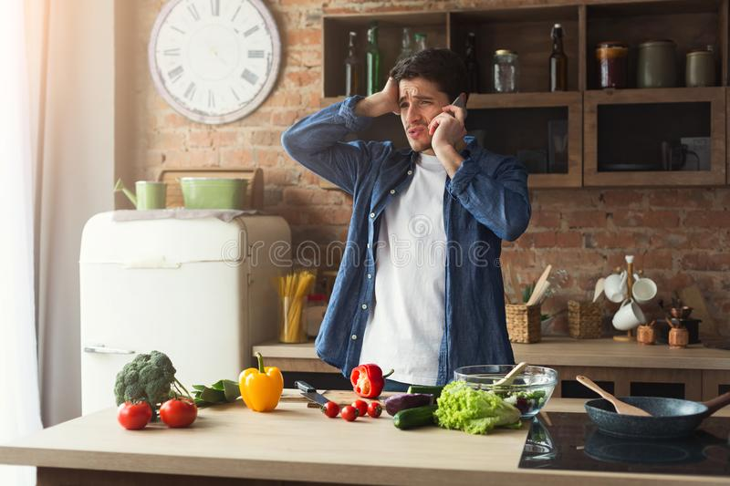 Disappointed man preparing healthy food in the home kitchen royalty free stock photos