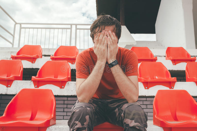 Disappointed man at sport stadium watching the game. In disbelief while his team is losing the match royalty free stock image