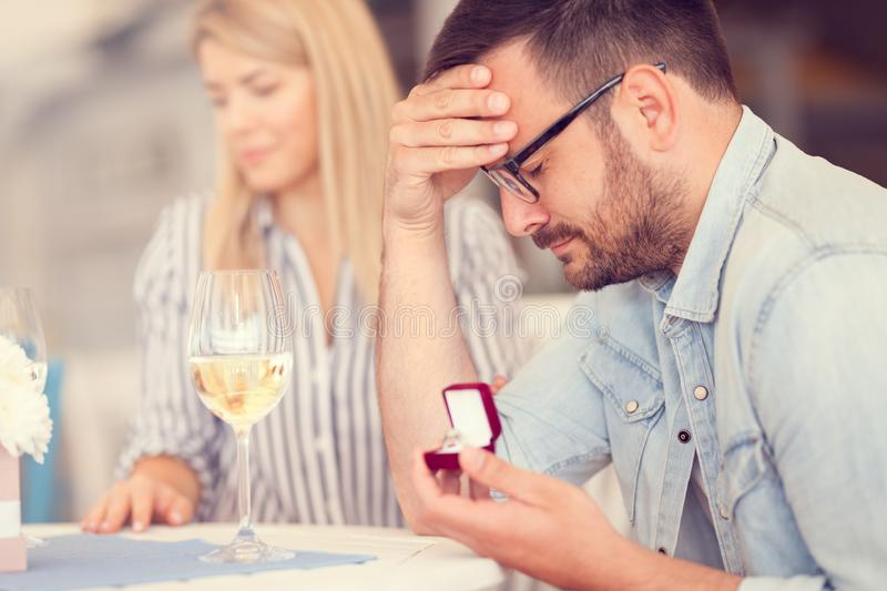 Disappointed man, woman refused his proposal. Unexpected moment of proposal, disappointed man, women refused his proposal royalty free stock image