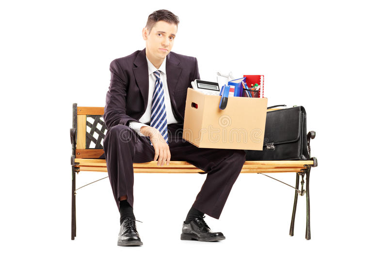 Disappointed redundant businessperson in black suit sitting on a. Bench with a box of belongings isolated on white background royalty free stock photography