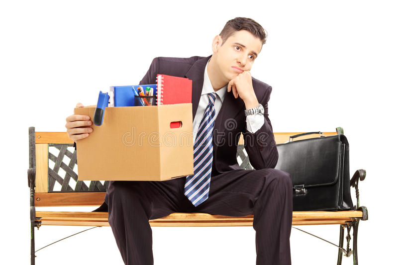 Disappointed redundant young man in a suit sitting on a bench. With a box of belongings isolated on white background royalty free stock photo
