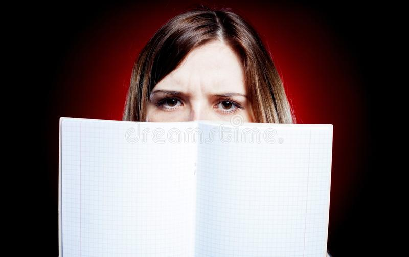 Disappointed and sad young girl holding exercise book royalty free stock image