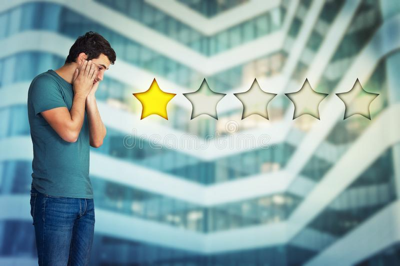 Disappointed. Side view of a disappointed and stressed young man hands on cheeks looking down choosing one star rating. Bad and poor customer service concept stock images