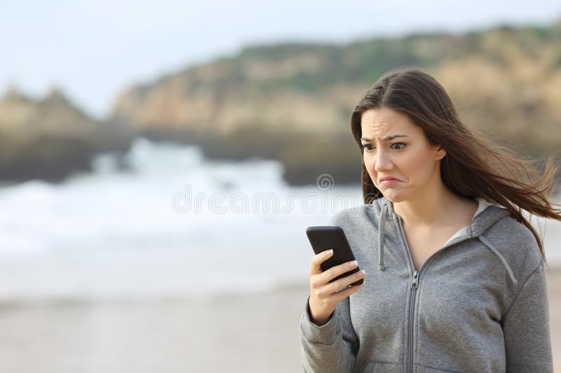 Disappointed teen reading phone message on the beach stock image