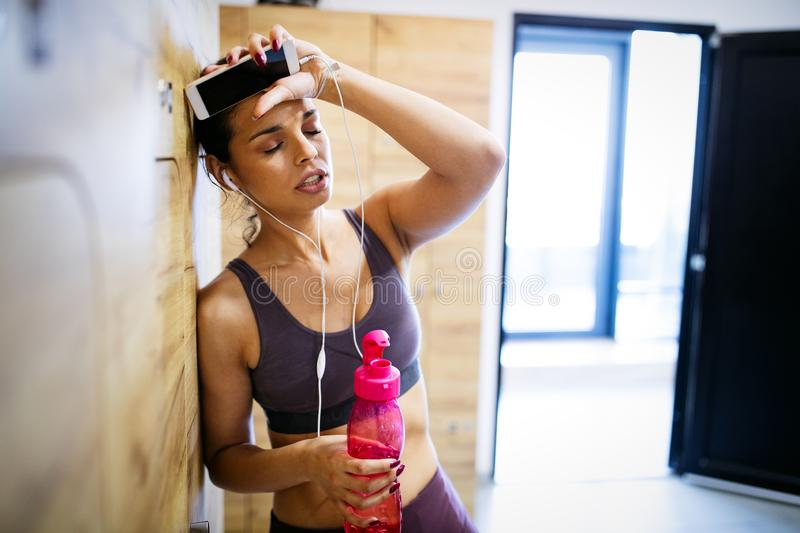 Disappointed tired woman trying to reach fitness goals by endurance and stamina training. In gym royalty free stock photo