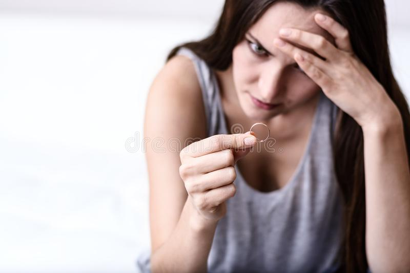 Disappointed wife depressed after divorce, holding a wedding ring sitting on a white sofa stock images