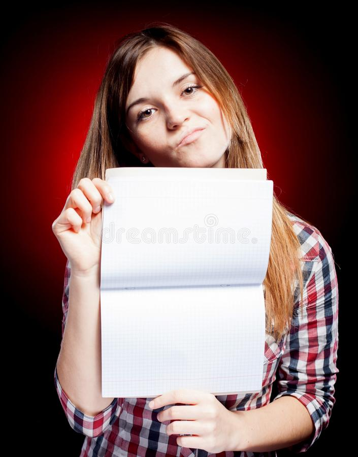 Disappointed young girl holding exercise book stock images