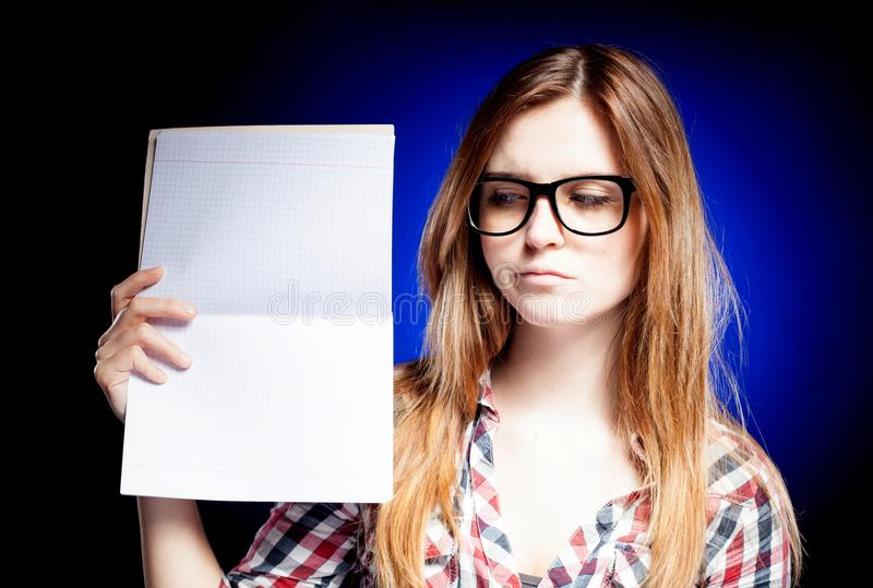 Disappointed young girl with nerd glasses holding royalty free stock photo