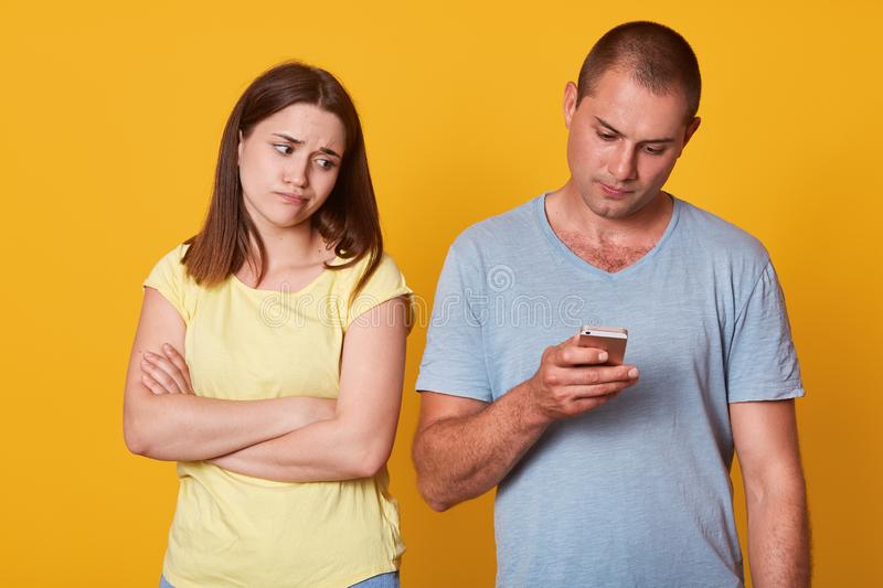 Disappointed young girl tired of being alone, looking at her boyfriend focused on his device, standing with folded arms. Busy. Handsome men paying no attention stock photo