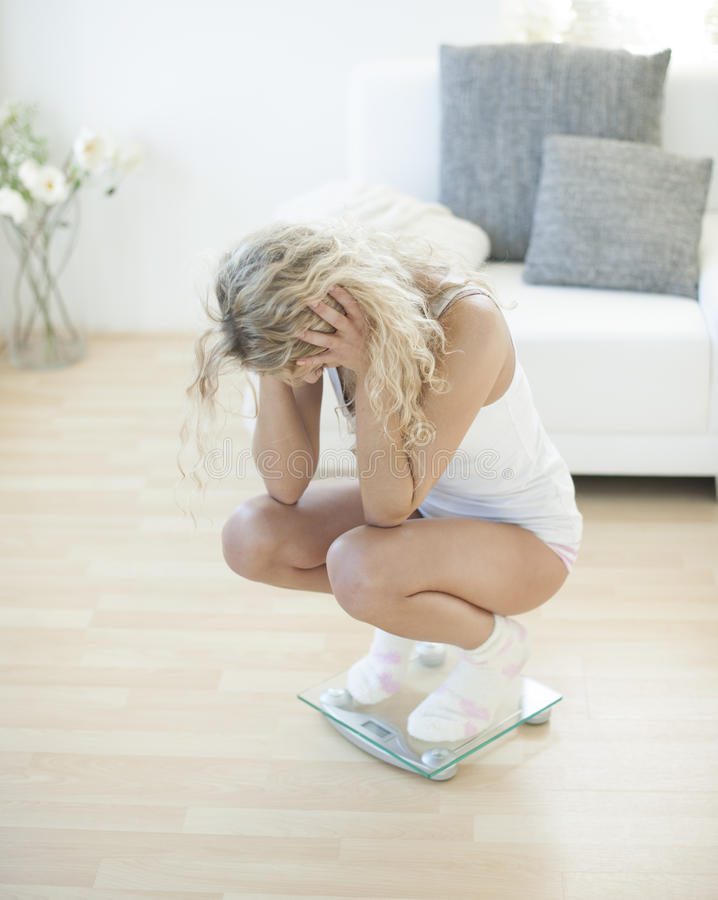 Disappointed young woman crouching on weighing scale stock image