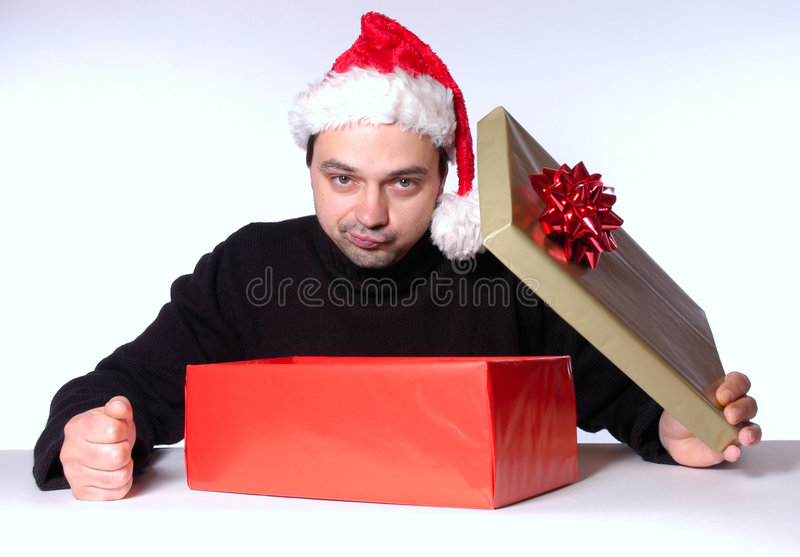 Disappointing present. Man with santa hat is disappointed about his present royalty free stock photography