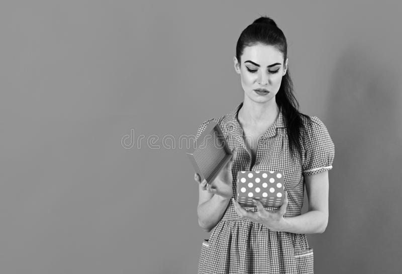 Disappointment and emotions concept. Woman opens gift box and feels disappointment royalty free stock image
