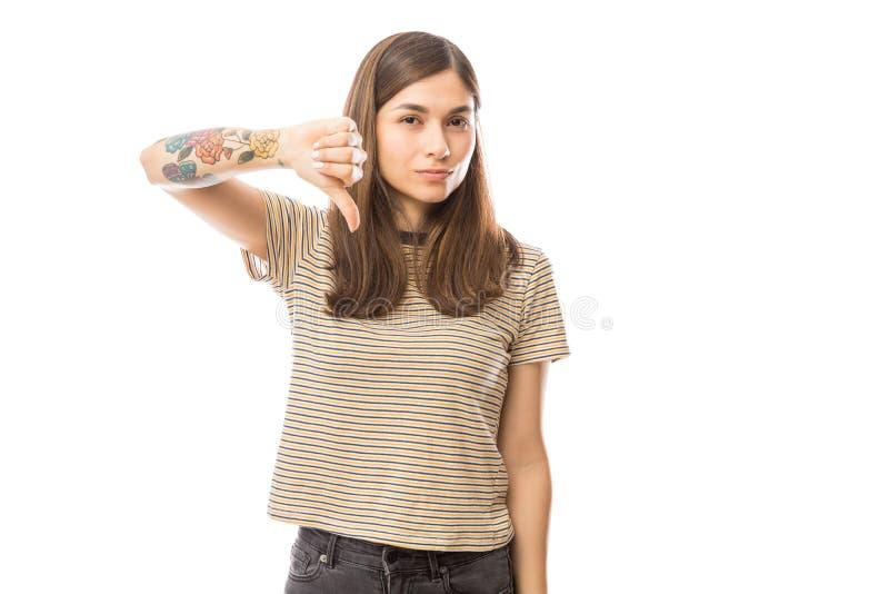 Disapprovazione di mostra femminile con i pollici giù su fondo bianco fotografia stock