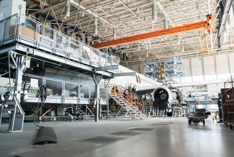 Disassembled airplane for repair and modernization in jet hangar. This airplane is disassembled to basic parts and workers and engineers are performing repairs royalty free stock photography