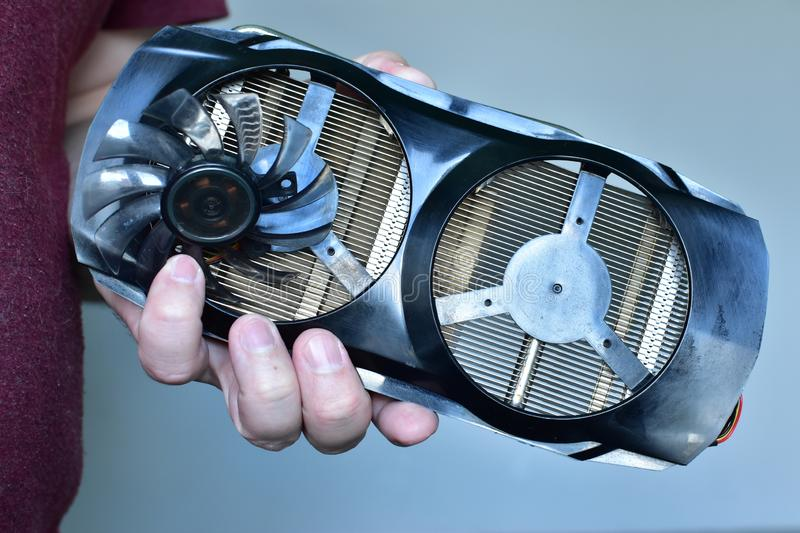 Disassembled broken video card of a personal computer and a screwdriver close-up man holding stock photos