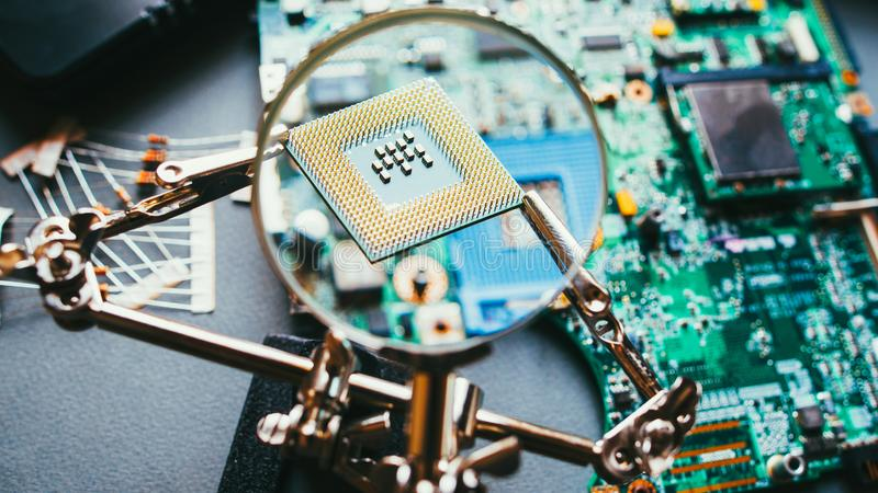 Disassembled computer components cpu processor. Disassembled computer components. CPU processor analysis through magnifying glass. PC electronic parts stock photos