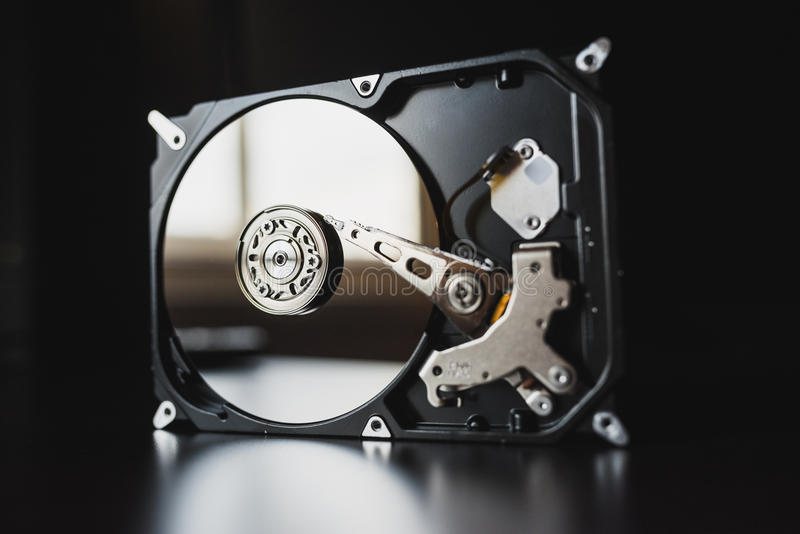 Disassembled hard drive from the computer (hdd) with mirror effects. Part of computer (pc, laptop). Opened hard drive from the computer (hdd) with mirror effects stock photo