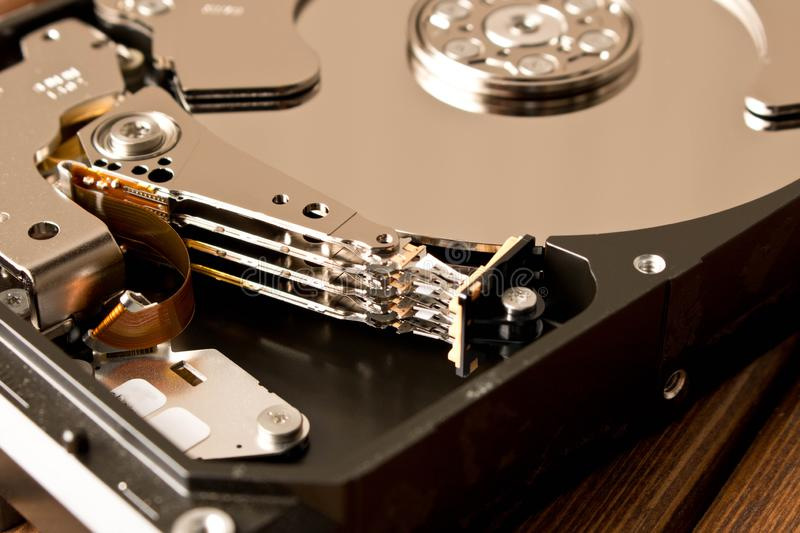 Disassembled hard drive on wooden table . Close up stock images
