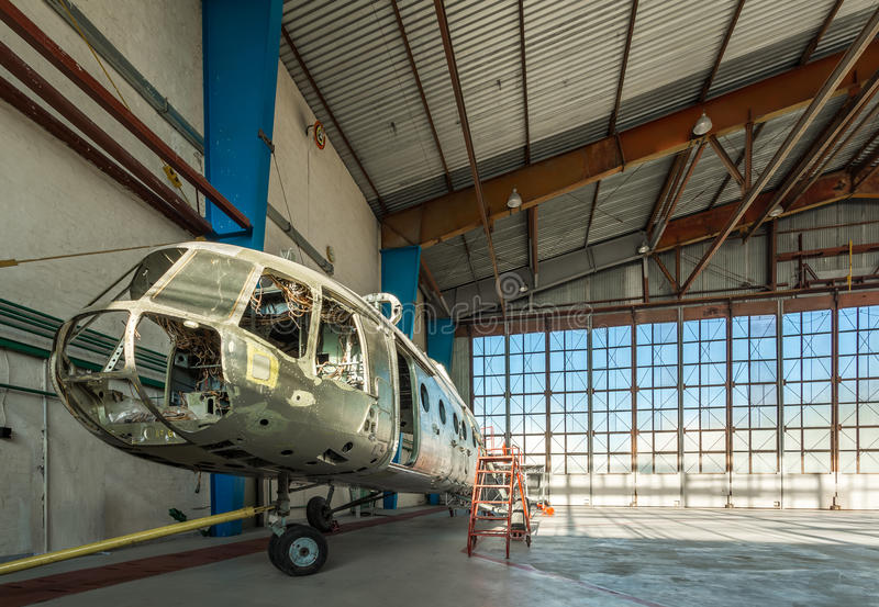 Disassembled helicopter repair stand in the hangar. Disassembled helicopter in repair stand in the air hangar. Aircraft without internal details, seats and trim stock photo