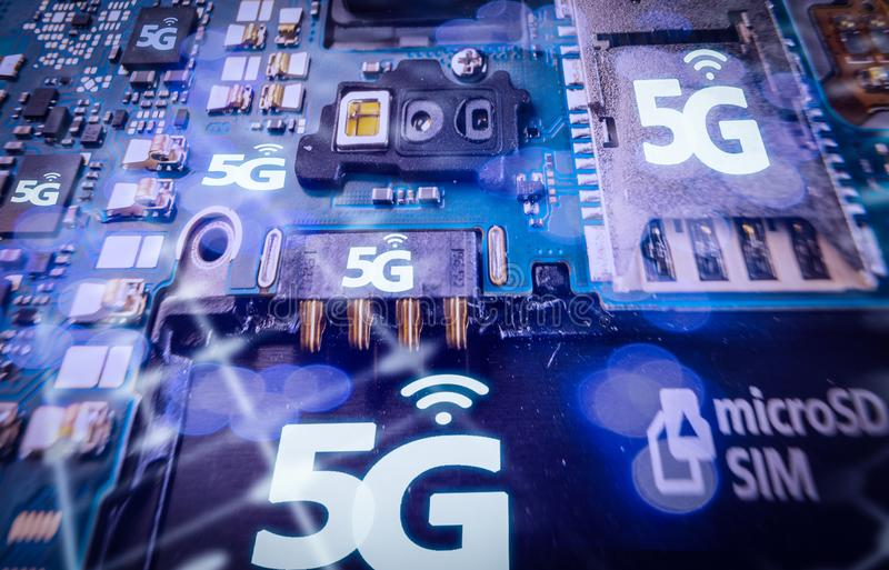 Disassembled mobile phone or smartphone without a back cover, and 5G or LTE word printed in circuit board. Macro shot. Disassembled mobile phone or smartphone stock image